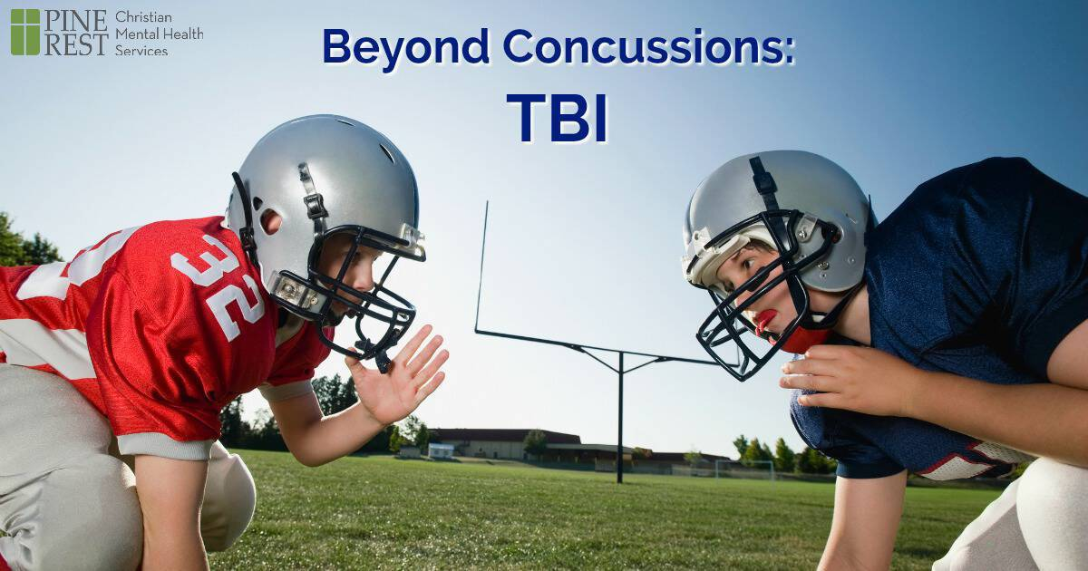 Two young boys facing off in football helmets