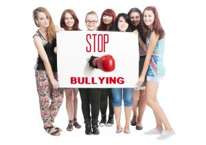 Stop Bullying concept text on white cardboard help by teen girls