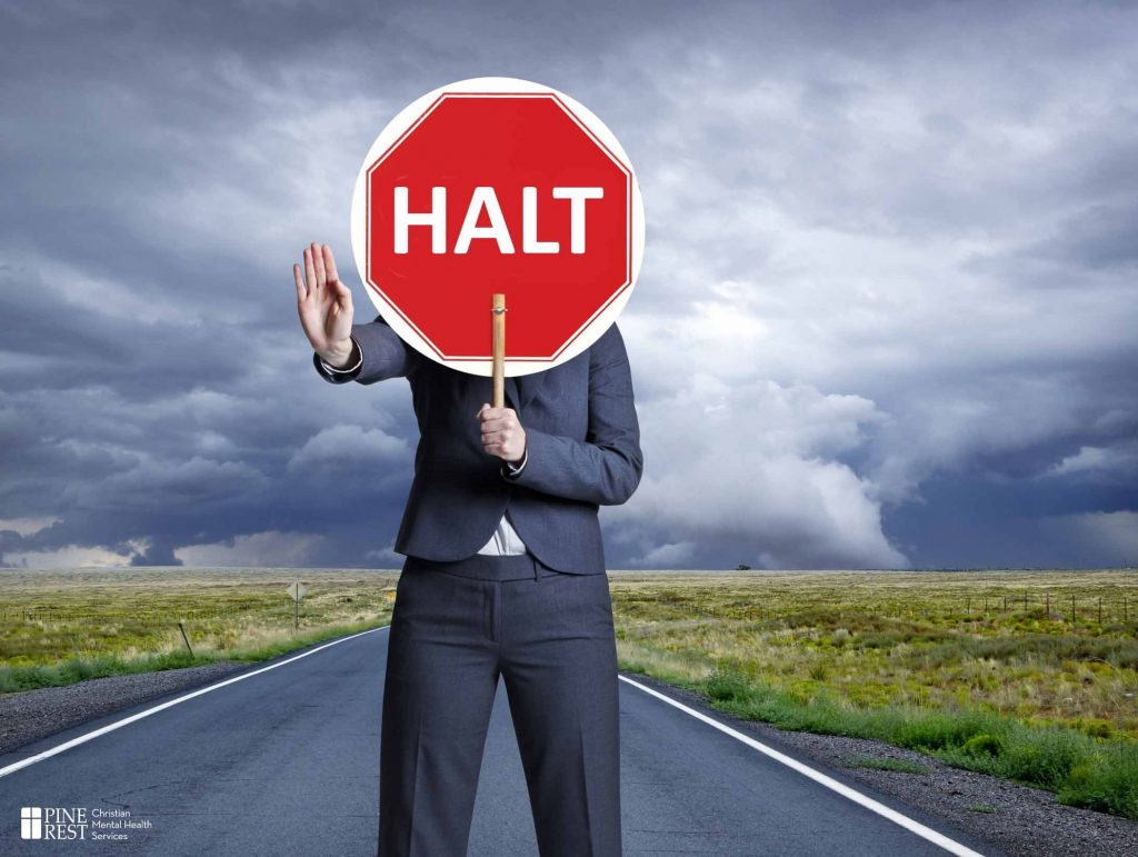 "Woman holding up a sign reading ""HALT"""