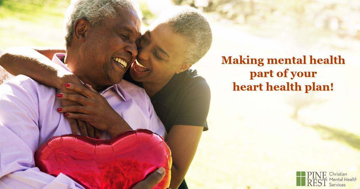 Older couple embracing while holding a heart shaped balloon