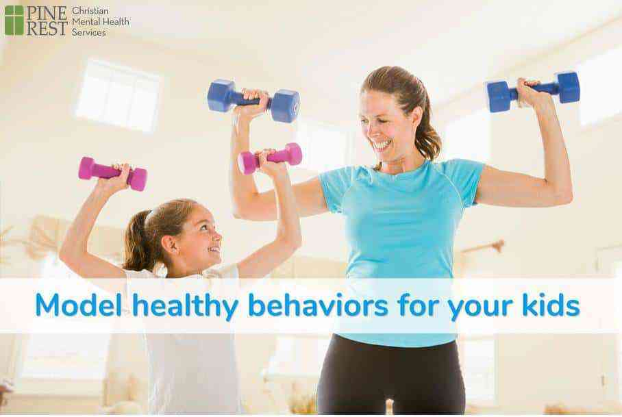 Mother and young daughter lifting barbells together at home