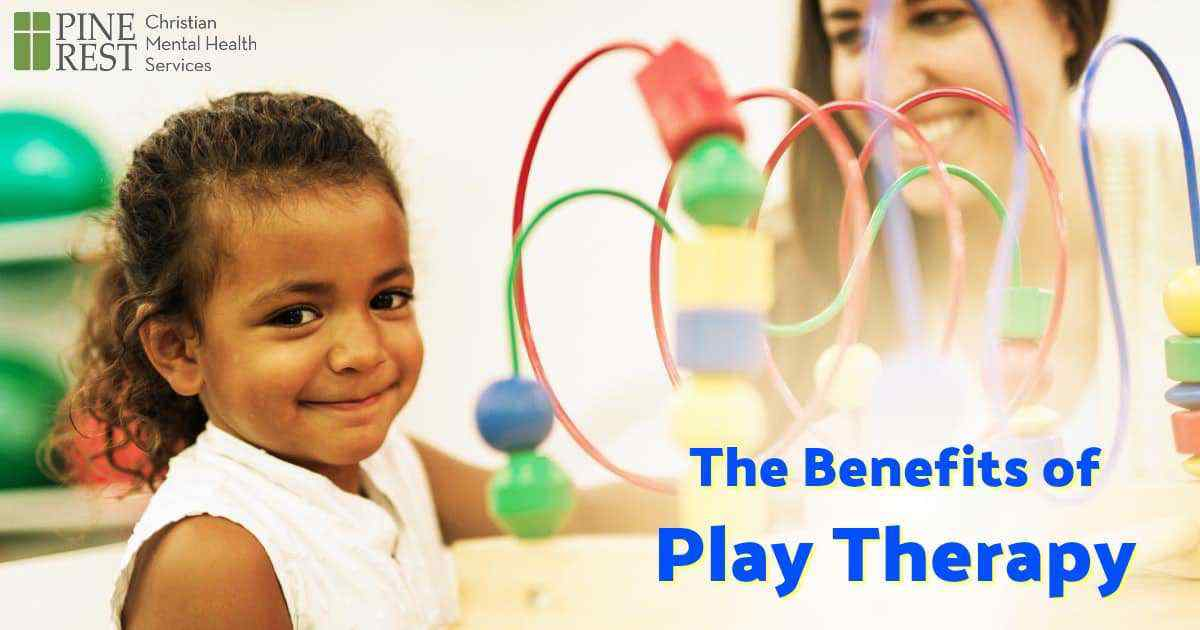 Preschool age girl playing with a toy alongside a friendly child therapist