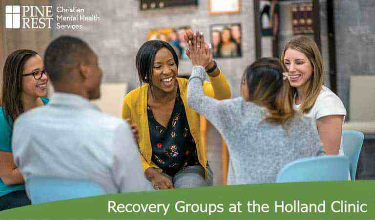 Group therapy participants high fiving each other