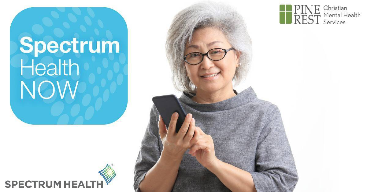 Middle aged woman smiling with mobile phone in hand against white background