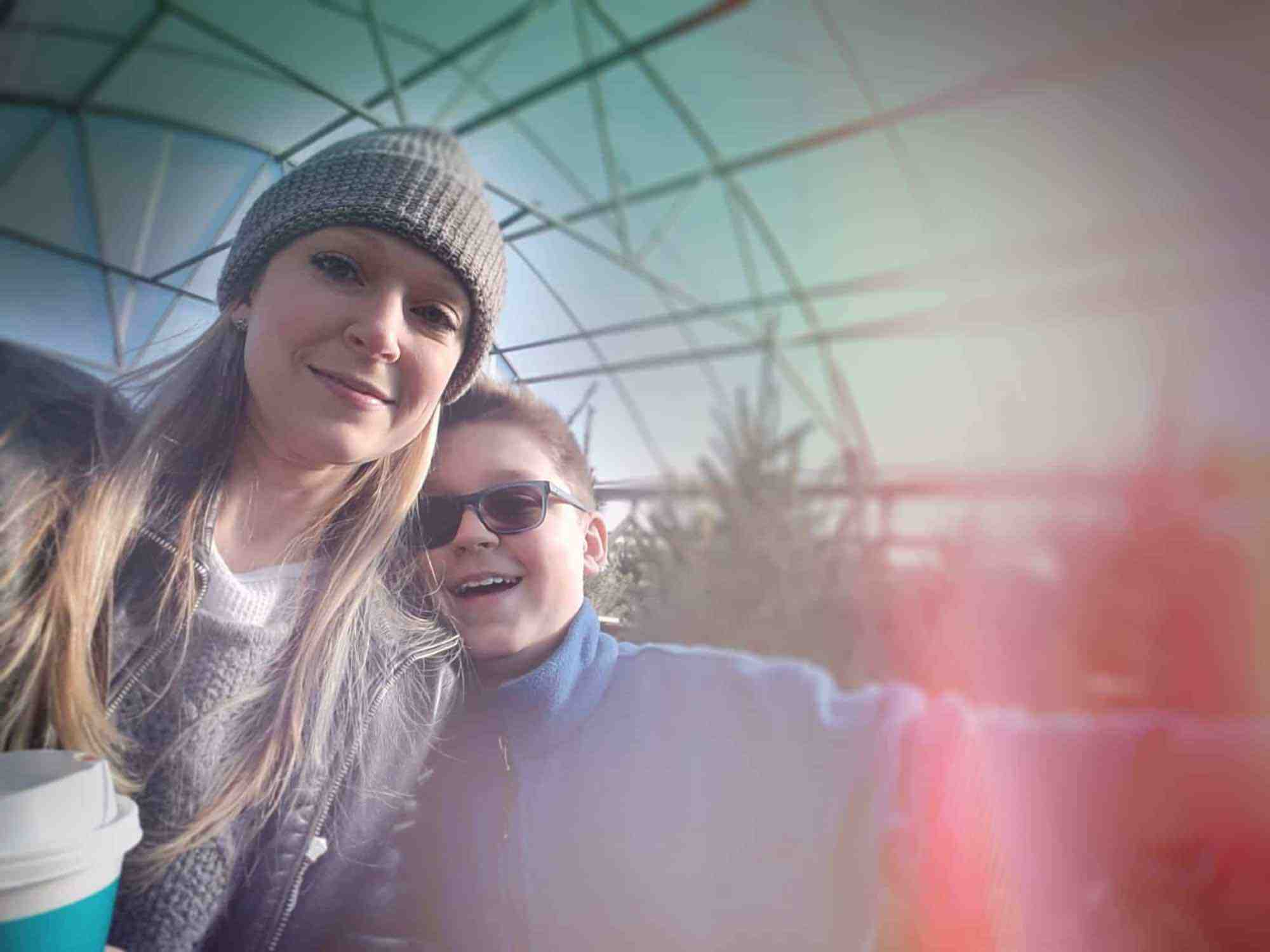 Story subject standing with her son in a Christmas tree greenhouse