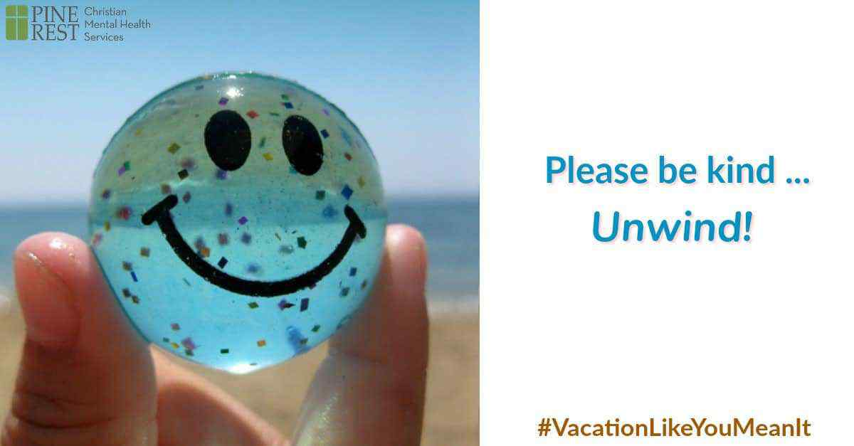 Person on beach holding beach ball with smiley face