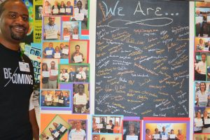 """""""I am the Patient Experience.""""  At the annual Hospital Based Services skills fair, Dante Griffin, Quality, talked with staff about the definition of patient experience and how all staff members are part of the experience no matter what discipline or in which department they work. His poster pictures staff members holding signs reading, """"I am the patient experience."""""""