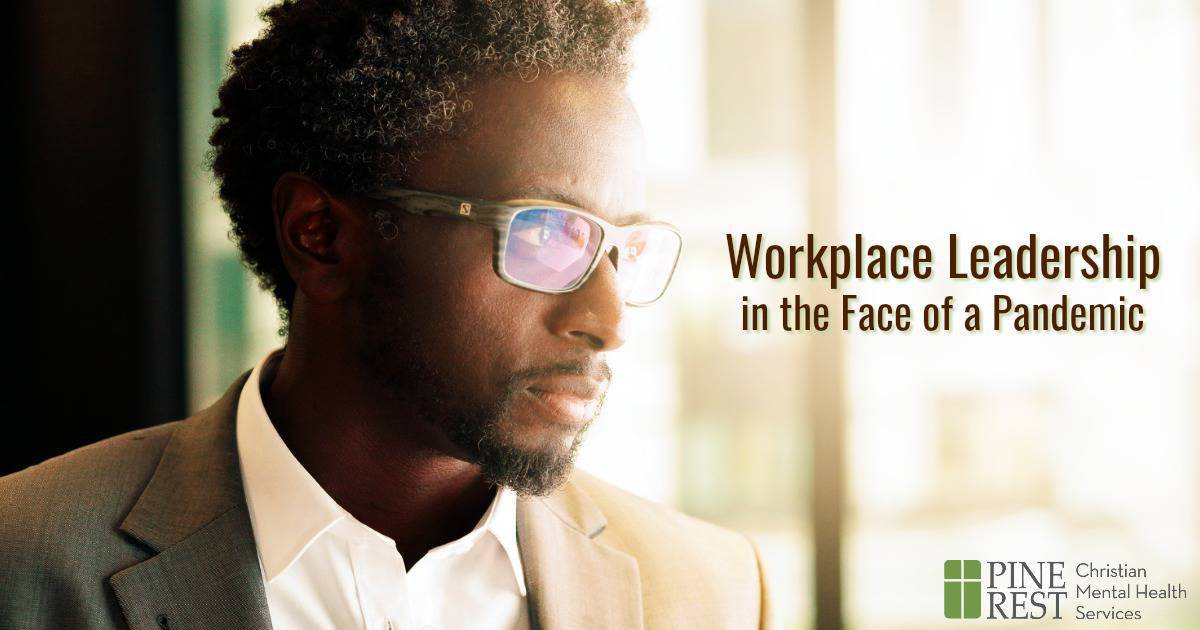 Young black professional man looking out office building window